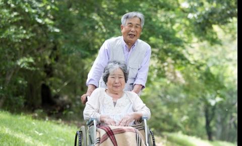 Asian man pushing his wife in a wheelchair